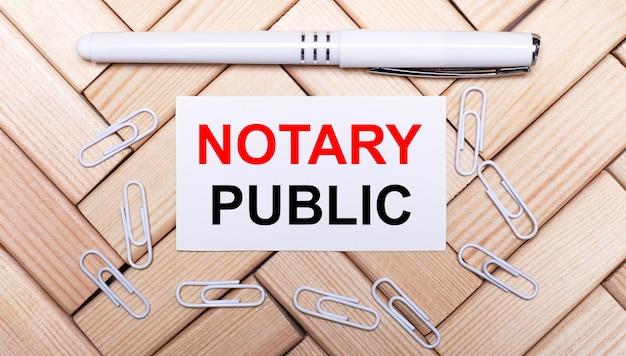 Auf einer oberfläche aus holzklötzen ein weißer stift, weiße büroklammern und eine weiße karte mit dem text notary public