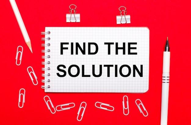 Auf einer roten oberfläche ein weißer stift, weiße büroklammern, ein weißer stift und ein notizbuch mit dem text find the solution