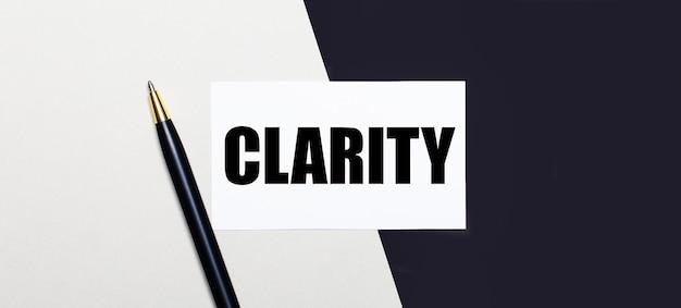 Auf einer schwarz-weißen oberfläche liegen ein stift und eine weiße karte mit dem text clarity