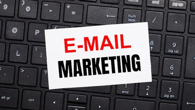 Auf einer schwarzen computertastatur befindet sich eine weiße karte mit dem text e-mail marketing