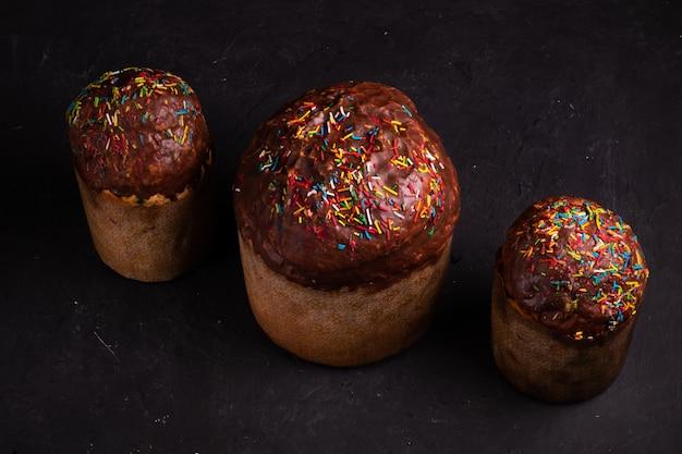 Auf einer schwarzen oberfläche stehen drei mit schokolade und süßigkeiten bestreute osterkuchen