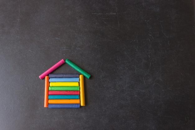 Auf einer schwarzen schultafel sind helle pastellstifte in form eines hauses angeordnet. kreativität für kinder. hintergrund mit exemplar