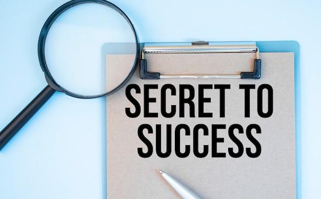 Auf einer weißen hintergrundlupe, einem stift und einem blatt papier mit dem text secret to success . geschäft