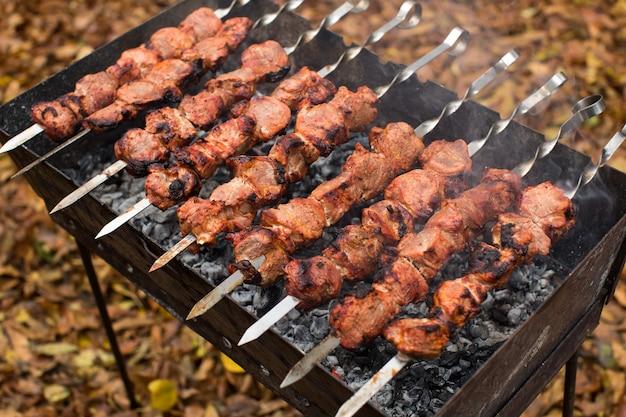 Auf feuer gebratenes fleisch grillspieße auf dem grill