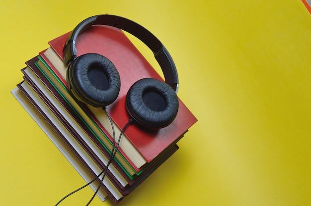Auf gelbem grund stehen ein stapel bücher und große, schwarze kopfhörer.