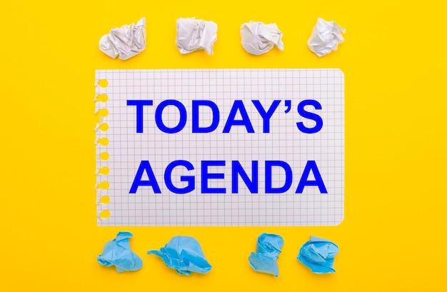 Auf gelbem grund weiße und blaue zerknitterte zettel und ein notizbuch mit dem text heute ist agenda