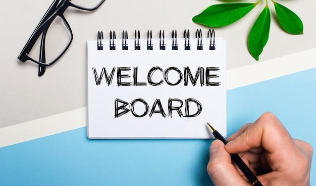 Auf graublauem hintergrund, neben einer brille und einem grünen blatt einer pflanze, schreibt ein mann auf ein blatt papier den text welcome board. flach liegen. von oben betrachten.
