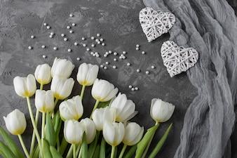 Auf grauem Hintergrund liegen weiße Tulpen, Perlen und zwei weiße Herzen