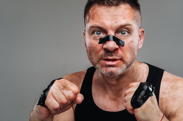 Auf grauem hintergrund steht ein ramponierter mann in einem schwarzen t-shirt, der wie ein kämpfer aussieht und sich auf einen kampf vorbereitet