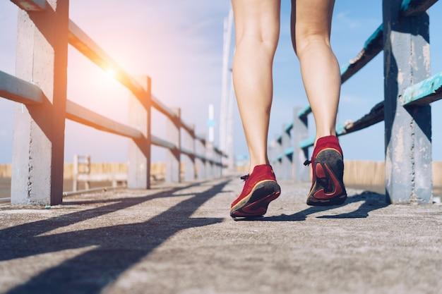 Auf grünem hintergrund geht und läuft eine frau mit laufschuhen. bewegung für die gesundheit ist ein begriff.