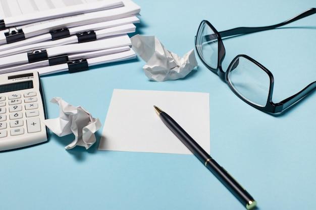Auf hellblauem hintergrund befinden sich dokumente, brillen, ein taschenrechner und papier mit einem stift. arbeitsplatznahaufnahme. geschäftskonzept