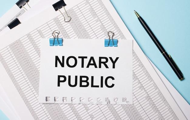 Auf hellblauem hintergrund dokumente, ein stift und ein blatt papier auf blauen büroklammern mit dem text notary public. unternehmenskonzept.
