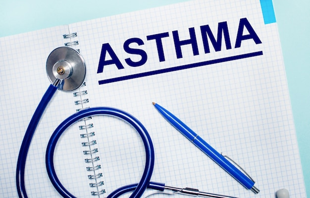Auf hellblauem hintergrund ein offenes notizbuch mit dem wort asthma, ein blauer stift und ein stethoskop