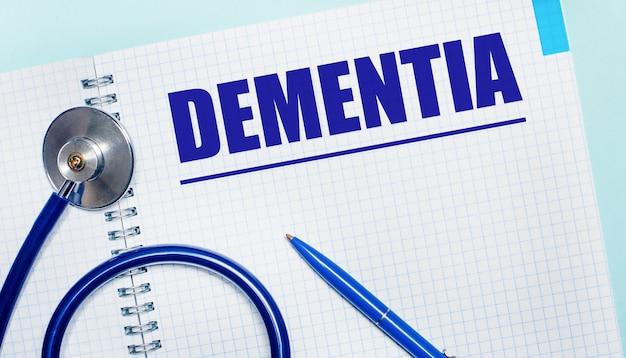 Auf hellblauem hintergrund ein offenes notizbuch mit dem wort dementia, ein blauer stift und ein stethoskop. sicht von oben. medizinisches konzept