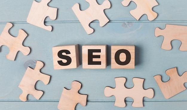 Auf hellblauem hintergrund liegen leere puzzles und holzwürfel mit der seo search engine optimization.