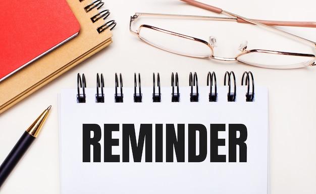 Auf hellem hintergrund - brille in goldrahmen, ein stift, braune und rote notizblöcke und ein weißes notizbuch mit dem text reminder.business concept