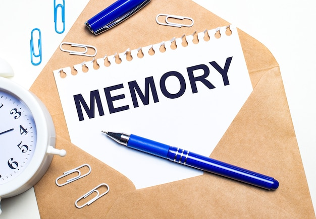 Auf hellem hintergrund ein bastelumschlag, ein wecker, büroklammern, ein blauer stift und ein blatt papier mit dem text memory.
