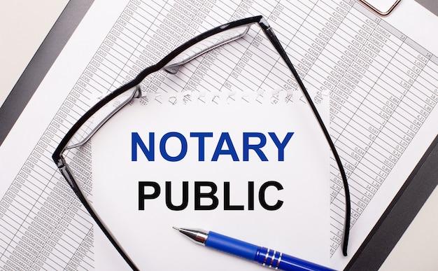 Auf hellem hintergrund ein bericht, eine schwarzgerahmte brille, ein stift und ein blatt papier mit dem text notary public. geschäftskonzept