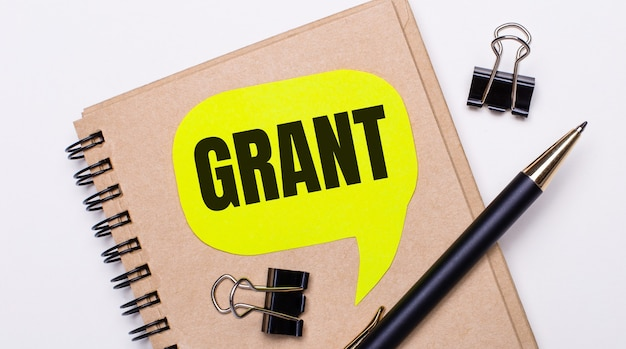 Auf hellem hintergrund ein braunes notizbuch, ein schwarzer stift und büroklammern und eine gelbe karte mit dem text grant. geschäftskonzept.