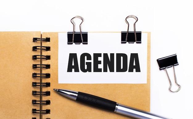 Auf hellem hintergrund ein braunes notizbuch mit stift, schwarzen klammern und einer weißen karte mit dem text agenda
