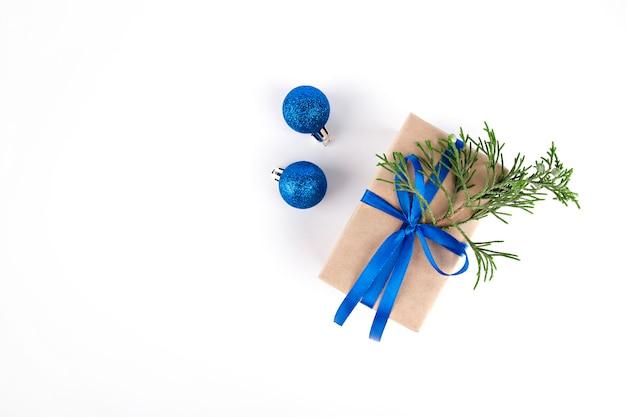 Auf hellem hintergrund ein geschenk mit blauem band, tannenzweig und blauen ornamenten