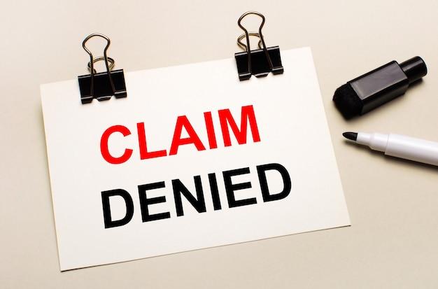 Auf hellem hintergrund ein schwarzer offener marker und auf schwarzen clips ein weißes blatt papier mit dem text claim denied