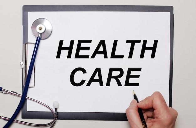 Auf hellem hintergrund ein stethoskop und ein blatt papier, auf das ein mann health care schreibt. medizinisches konzept