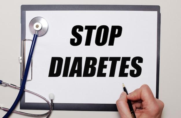 Auf hellem hintergrund ein stethoskop und ein blatt papier, auf dem ein mann stop diabetes schreibt. medizinisches konzept