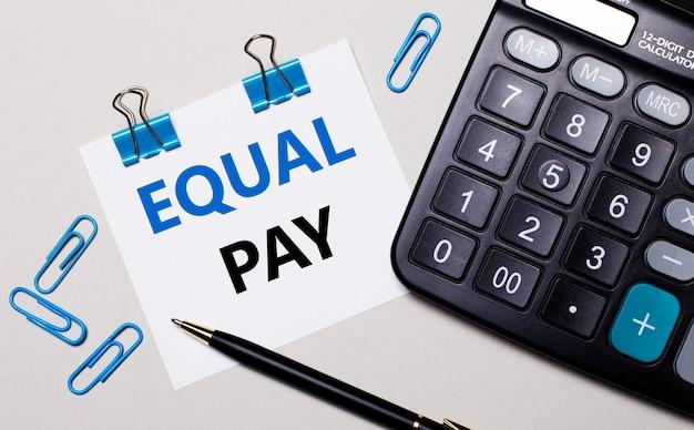 Auf hellem hintergrund ein taschenrechner, ein stift, blaue büroklammern und ein blatt papier mit dem text equal pay