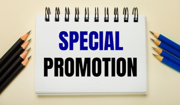 Auf hellem hintergrund ein weißes notizbuch mit dem text special promotion und schwarzen und blauen stiften an den seiten.