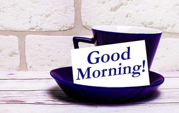 Auf hellem hintergrund eine blaue tasse mit untertasse und der aufschrift good morning.
