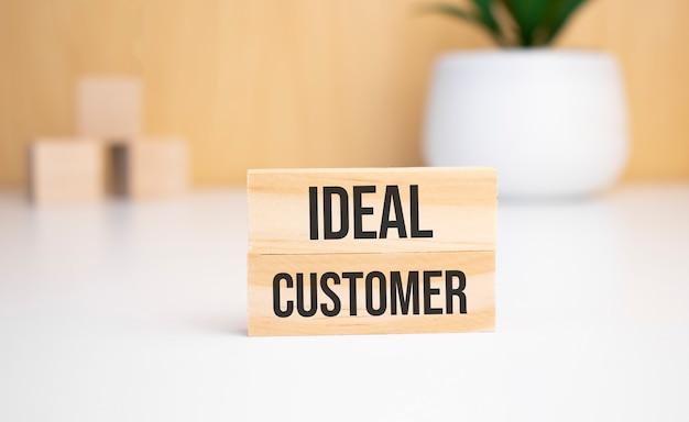 Auf hellem hintergrund holzwürfel und ein holzklotz mit dem text ideal customer. sicht von oben