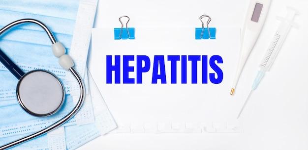 Auf hellem hintergrund liegen ein stethoskop, ein elektronisches thermometer, eine spritze, eine gesichtsmaske und ein blatt papier mit dem text hepatitis. medizinisches konzept