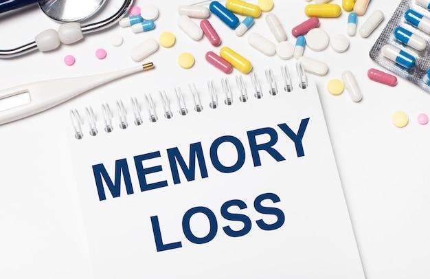 Auf hellem hintergrund mehrfarbige pillen, ein stethoskop, ein elektronisches thermometer und ein notizbuch mit dem text memory loss. medizinisches konzept.