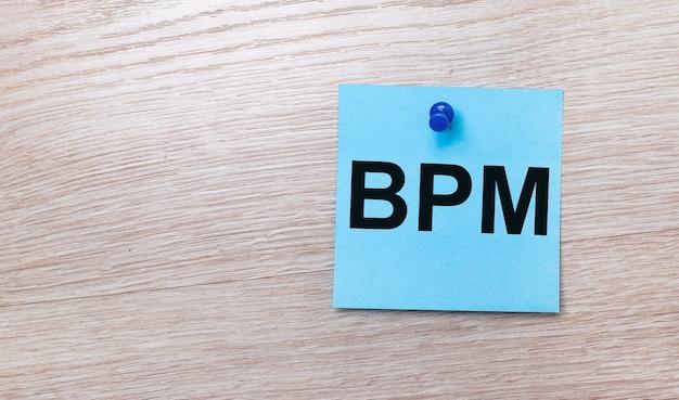 Auf hellem holzgrund - ein hellblauer quadratischer aufkleber mit dem text bpm business process management