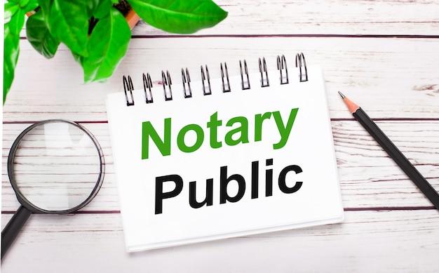 Auf hellem holzgrund eine lupe, ein bleistift, eine grüne pflanze und ein weißes notizbuch mit dem text notary public. geschäftskonzept