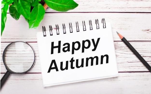 Auf hellem holzhintergrund eine lupe, ein bleistift, eine grüne pflanze und ein weißes notizbuch mit dem text happy autumn. geschäftskonzept