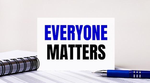 Auf hellgrauem hintergrund ein notizbuch, ein blauer stift und ein blatt papier mit dem text everyone matters. geschäftskonzept