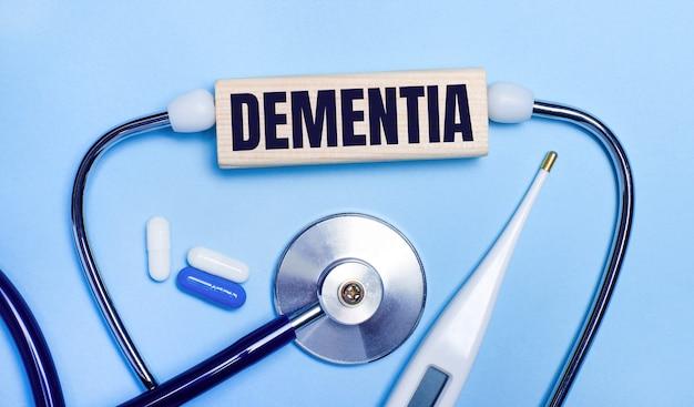 Auf hellgrauem hintergrund ein stethoskop, ein elektronisches thermometer, pillen, ein holzklotz mit dem text dementia. medizinisches konzept.
