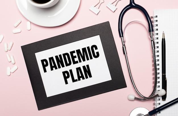Auf hellrosa hintergrund ein notizbuch mit stift, stethoskop, weißen pillen, büroklammern und einem blatt papier mit dem text pandemischer plan. medizinisches konzept