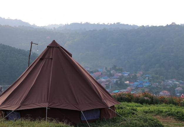 Auf hügel mit hellem nebel im sonnenuntergangzeitnatur-landschaftshintergrund kampieren