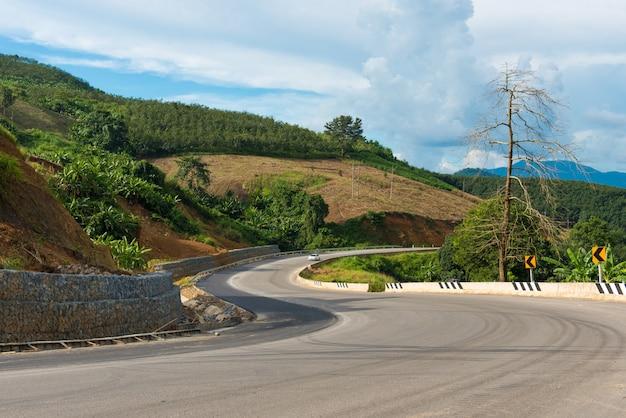 Auf hügelasphaltstraße mit auto und naturlandschaft des blauen himmels