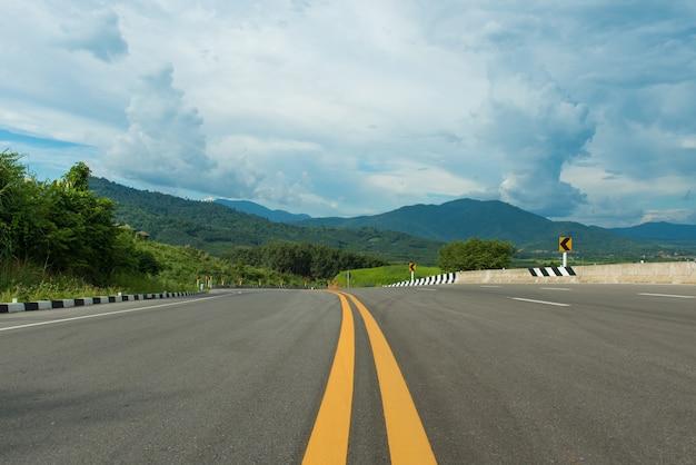 Auf hügelasphaltstraße und naturlandschaft des blauen himmels