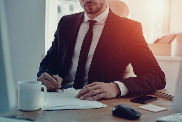 Auf jedes detail achten. nahaufnahme eines jungen mannes in abendkleidung, der die formulare ausfüllt, während er im büro sitzt sitting