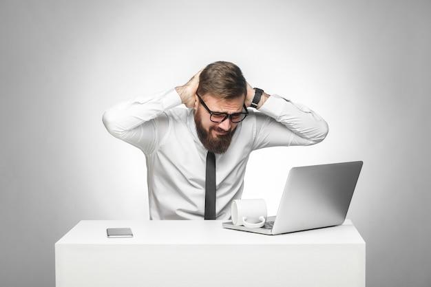 Auf keinen fall! porträt eines unheilvollen, schmerzhaften jungen managers in weißem hemd und schwarzer krawatte sitzen im büro und haben starke kopfschmerzen und halten die hände am kopf. studioaufnahme, isoliert, grauer hintergrund, innenbereich