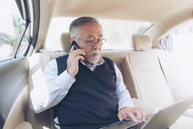 Auf lagerhändlerspieler des geschäfts älterer reicher mann in der klage, die mit laptop-computer arbeitet