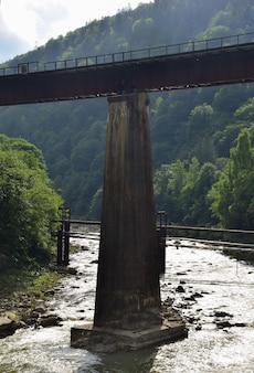 Auf langen betonsäulen erhebt sich eine fußgängerbrücke mit geländer über den turbulenten gebirgsfluss