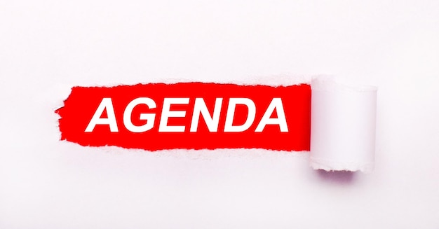 Auf leuchtend rotem grund weißes papier mit einem zerrissenen streifen und der aufschrift agenda.