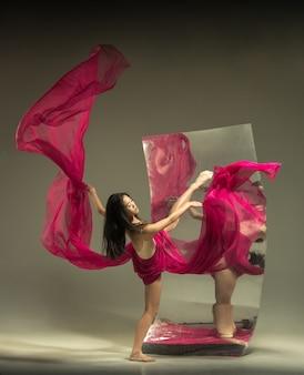 Auf meinem weg zum ideal. moderne balletttänzerin auf brauner wand mit spiegel. illusionsreflexionen auf der oberfläche. magie der flexibilität, bewegung mit stoff. konzept des kreativen kunsttanzens, der aktion, der inspiration.
