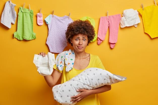 Auf neugeborene aufpassen. verwirrte lockige mutter hält windel, baby in decke, beschäftigt stillen, wäscht kinderkleidung, erledigt mütterarbeiten, isoliert auf gelber wand. multitasking mutter zu hause